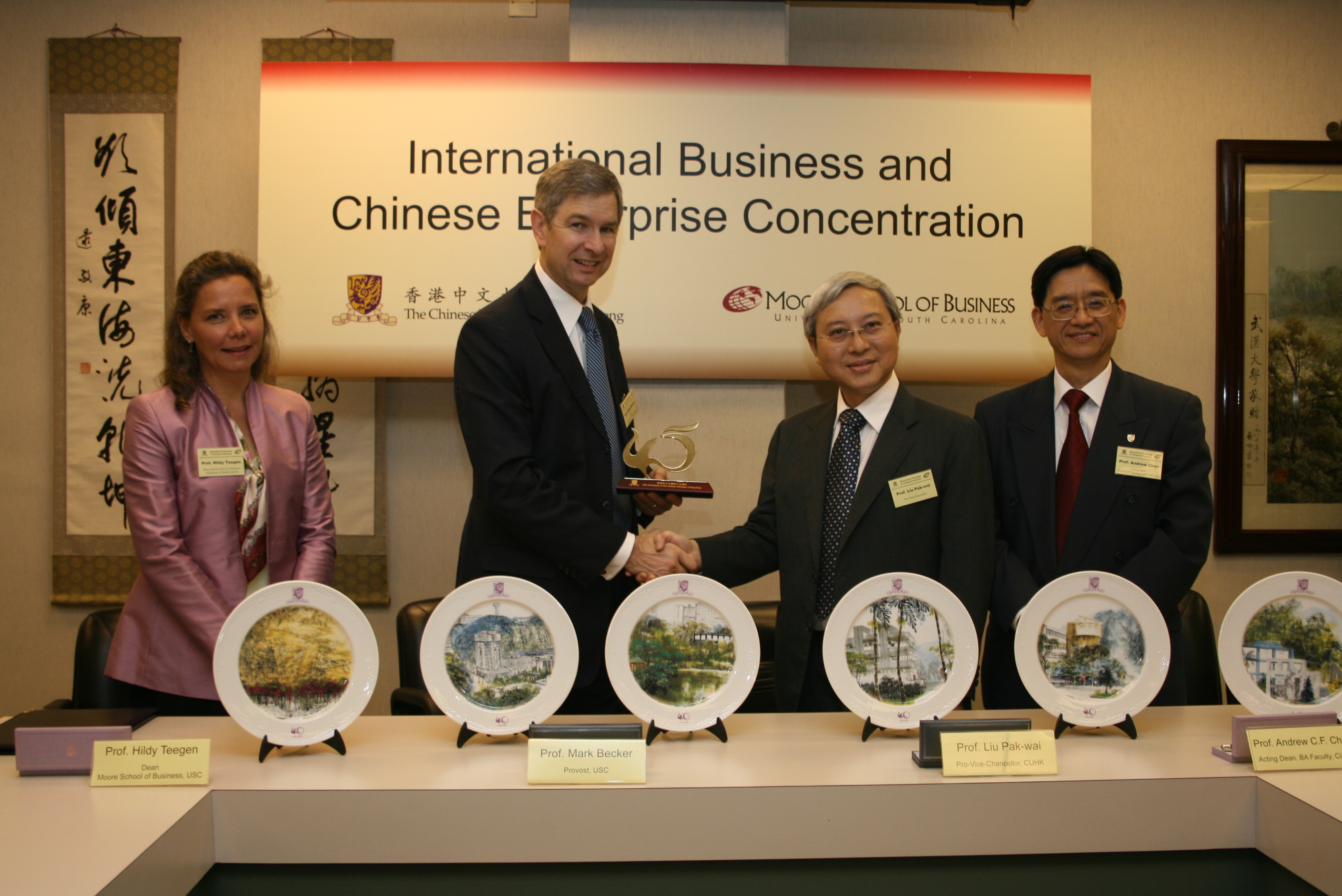 Prof. Prof. Liu Pak Wai, Pro-Vice-Chancellor of The Chinese University of Hong Kong (CUHK) presented CUHK 45th Anniversary souvenir to Prof. Mark Becker, Provost of the University of South Carolina. On the left is Prof. Hildy J. Teegen, Dean, Moore School of Business, University of South Carolina and on the right is Prof. Andrew Chan, Acting Dean, Faculty of Business Administration, CUHK.