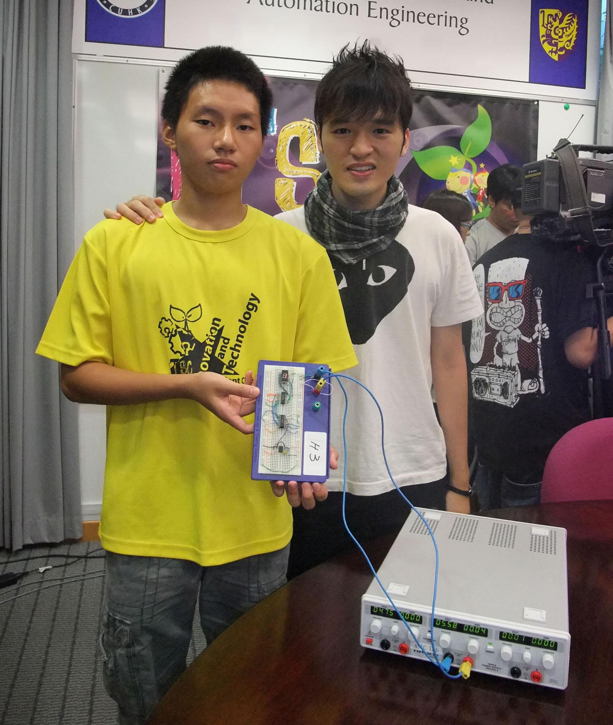 順德聯誼總會李兆基中學的中五學生楊育浚(左)在中大電子工程學系研究助理章覺文的指導下,製成電子時鐘