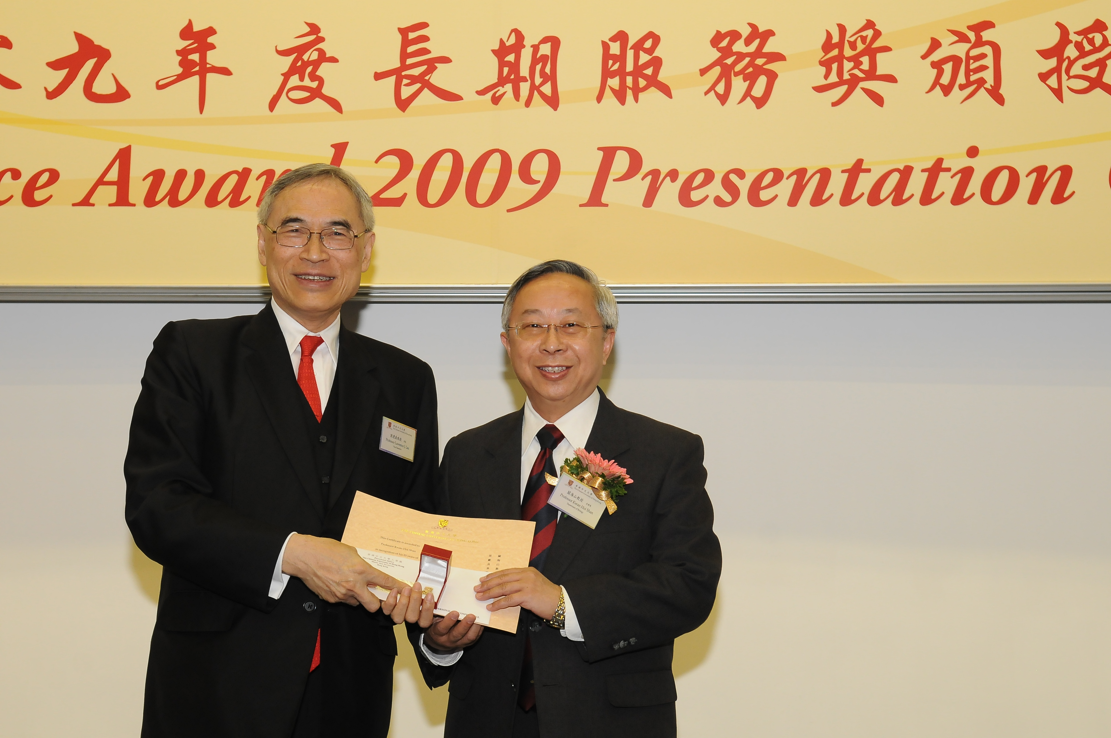 Prof. Lawrence J. Lau presents a certificate and a gold lapel pin to Prof. Kwan Hoi-shan, recipient of 25-year Long Service Award