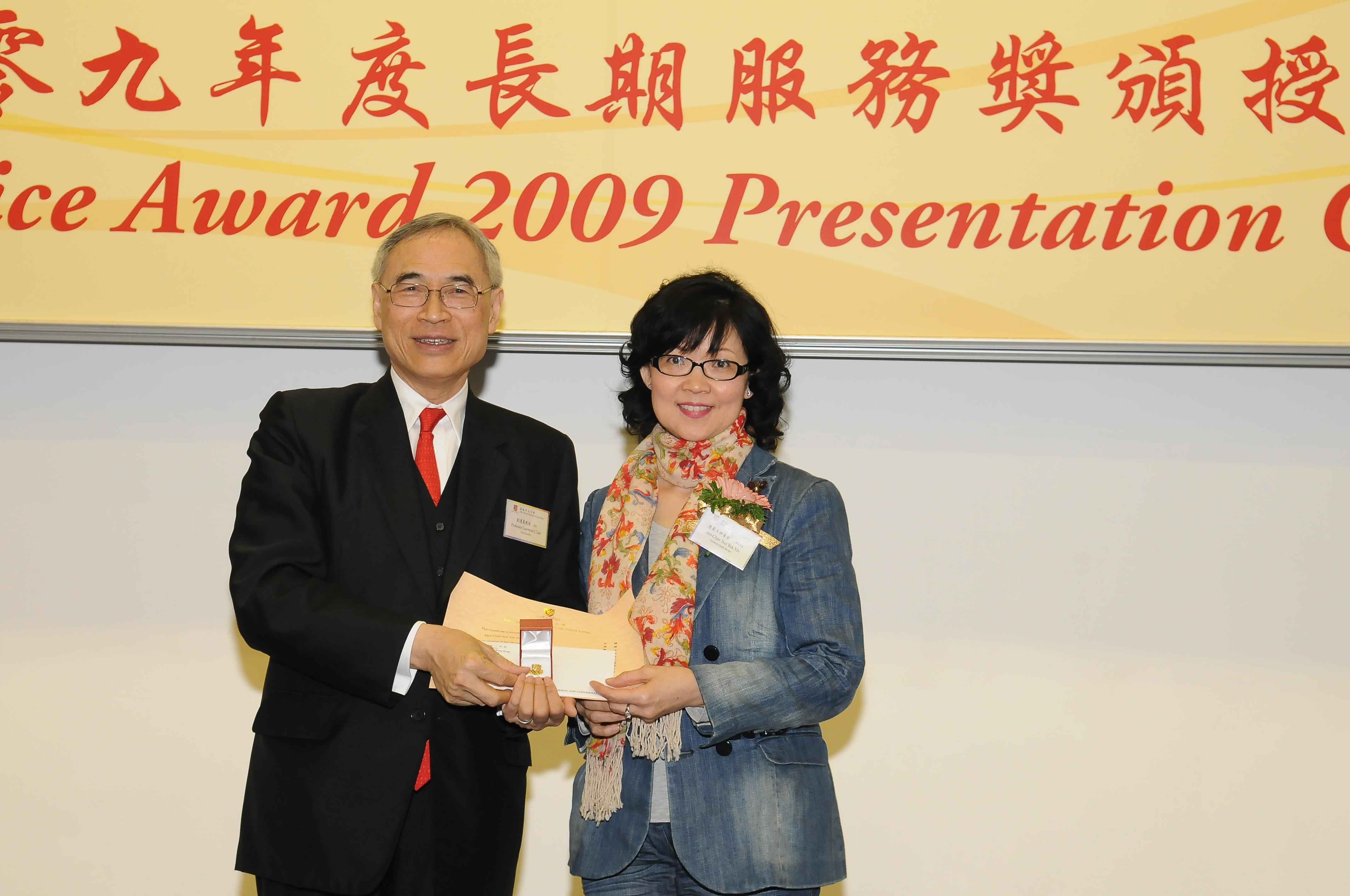 Prof. Lawrence J. Lau presents a certificate and a gold lapel pin to Mrs. Chan Tsoi Yuk-yin, recipient of 25-year Long Service Award