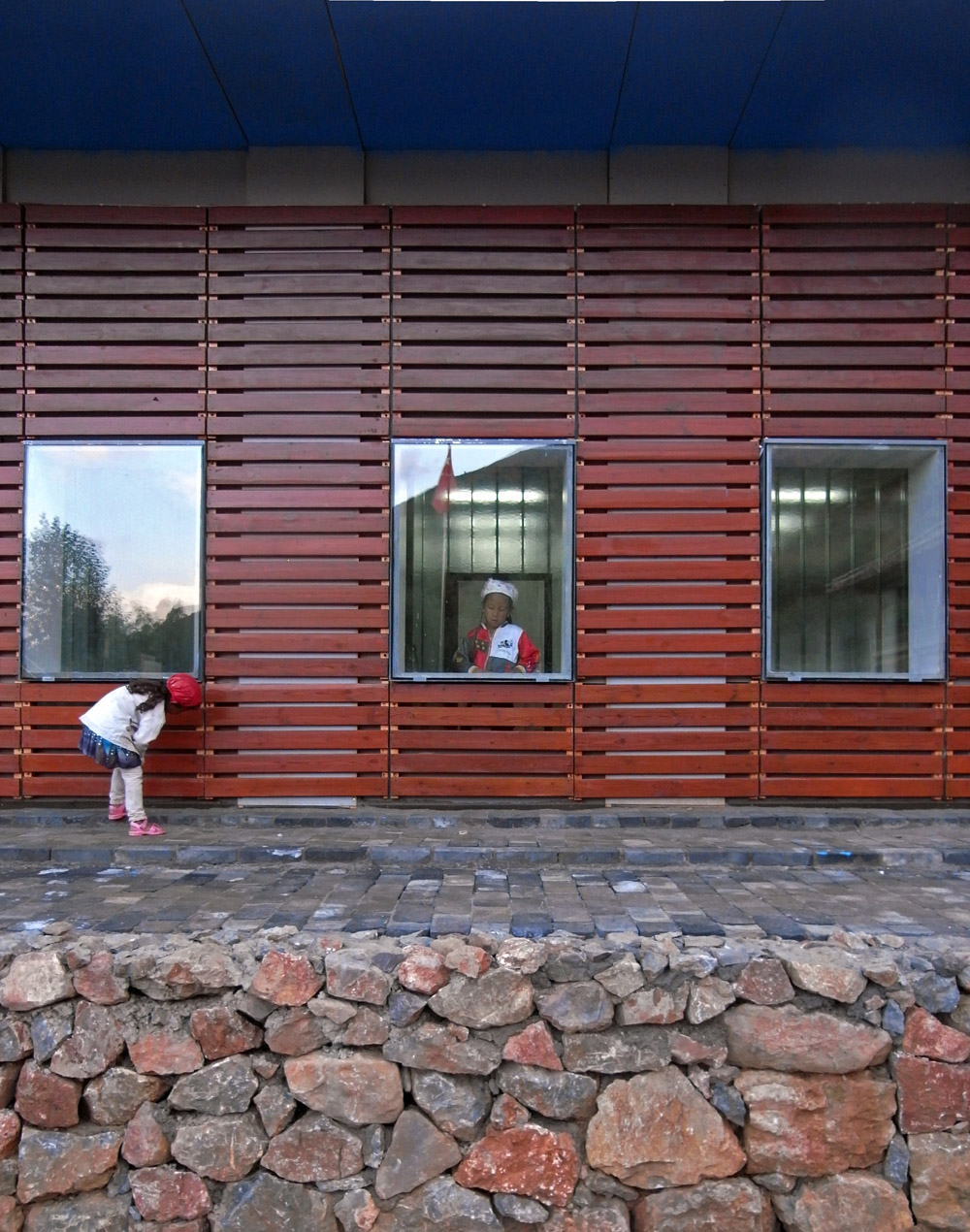 With a simple timber-trellis cladding design, this modern building blends in with the rural ambiance of the village