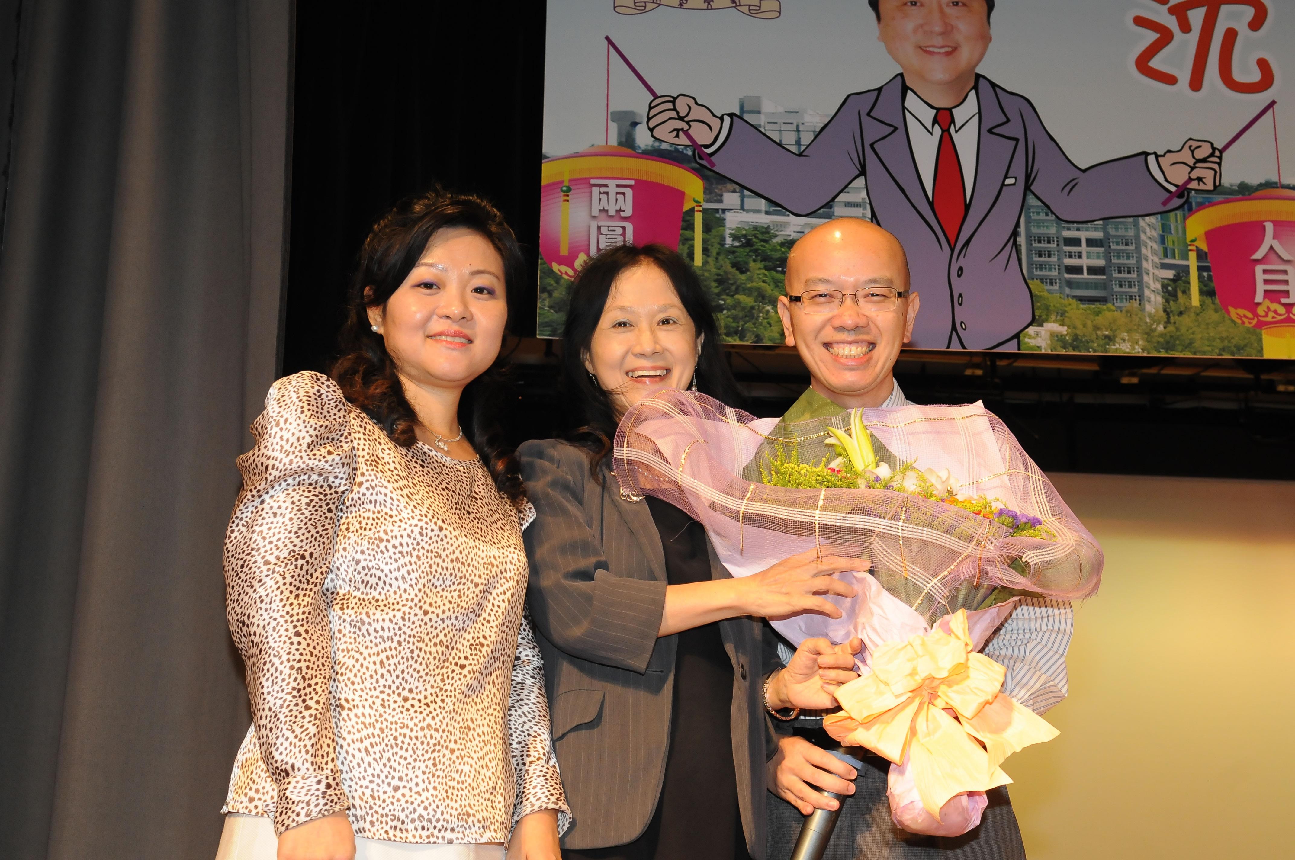 保健處處長陸偉昌醫生(右)演唱「月半彎」後,保健處同事獻花支持
