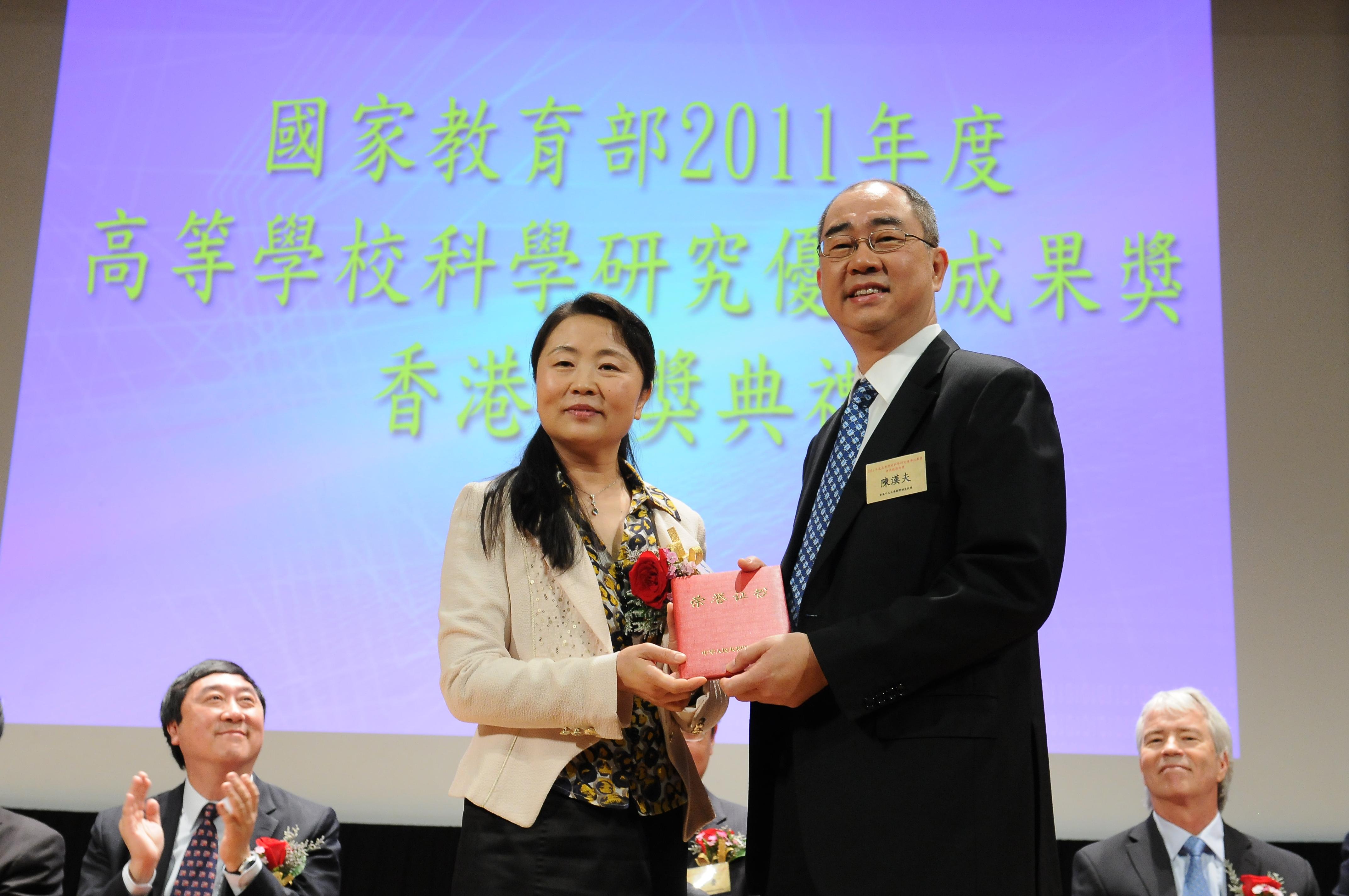 Prof. Chan Hon-fu Raymond, Professor, Department of Mathematics, CUHK, receives his award certificate from Dr. Zhou Jing.