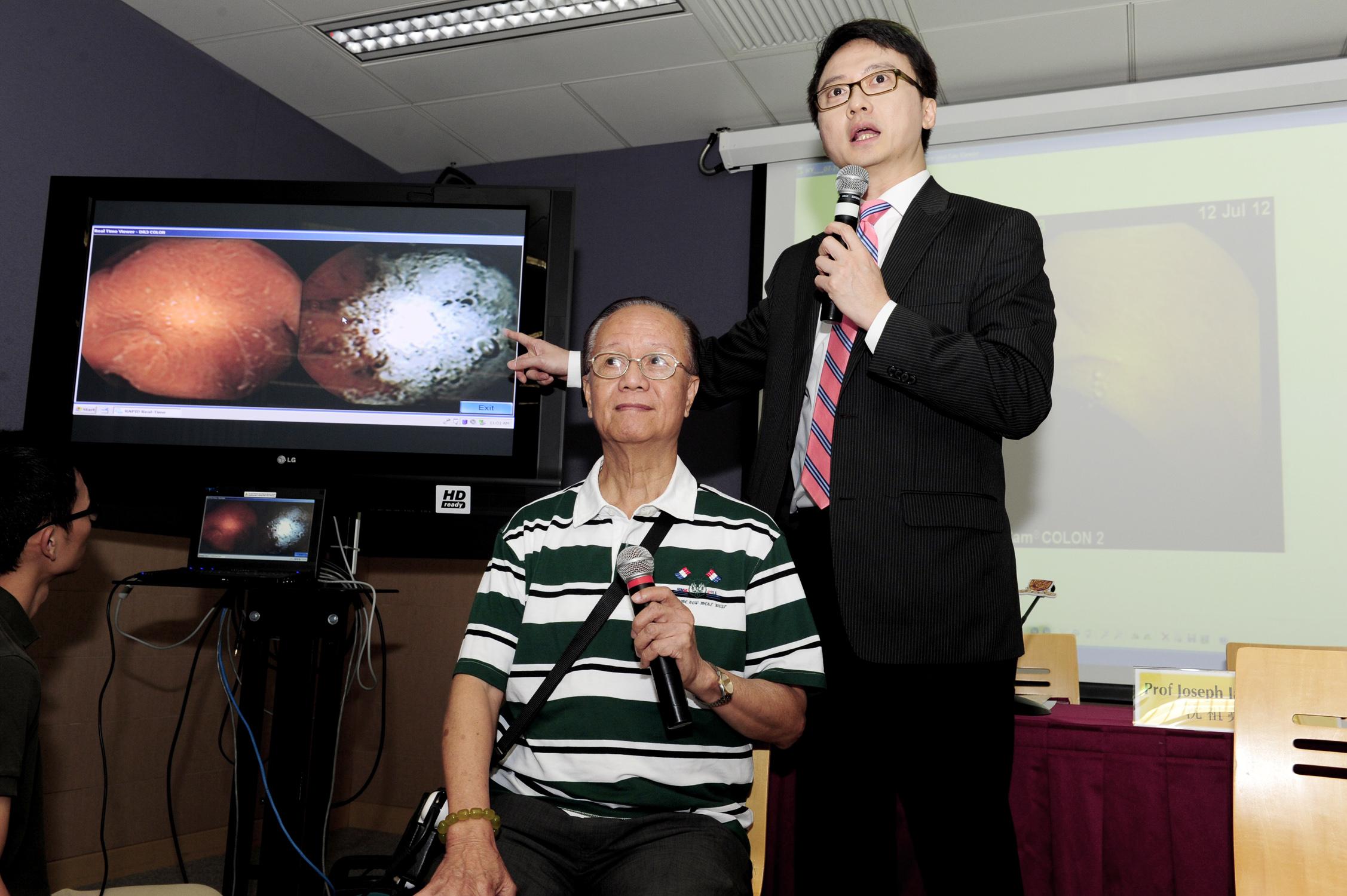 陳家亮教授(右)展示大腸膠囊內視鏡拍攝的實時影像