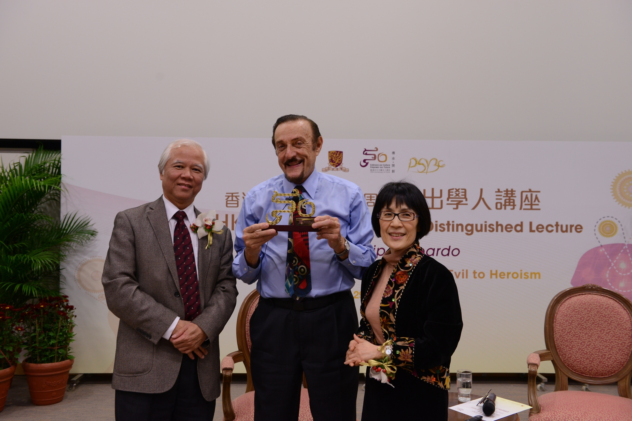 Prof. Paul Lee, Dean of Social Science (left) and Prof. Fanny Cheung, Choh-Ming Li Professor of Psychology, CUHK (right) present a souvenir to Prof. Philip Zimbardo.
