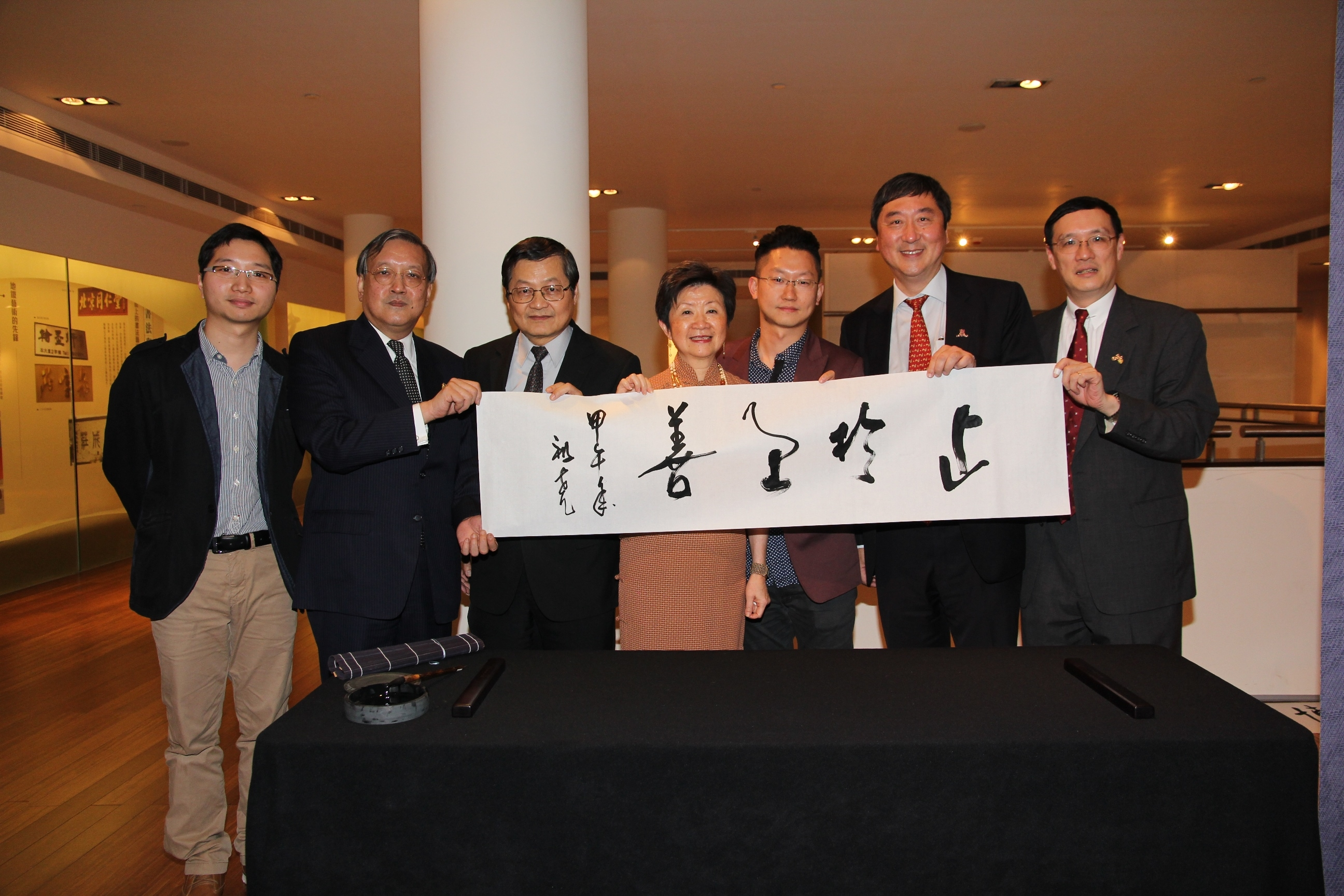 A group photo with Prof. Joseph Sung's calligraphy.