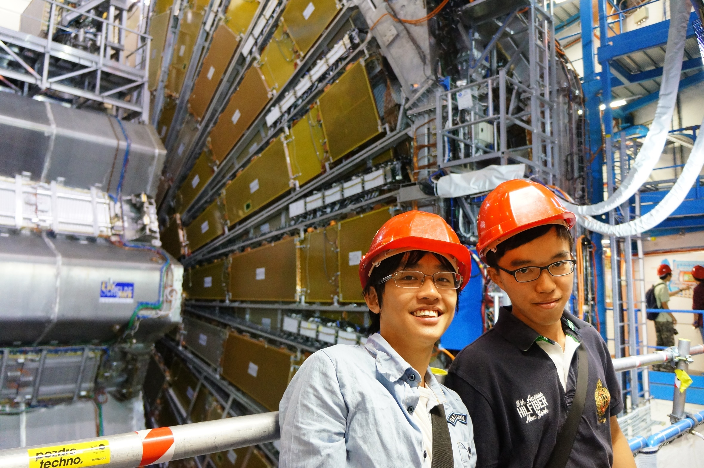 MPhil student Tsui Ka Ming and undergraduate student Tam Pok Ho in front of the ATLAS detector.  Both will be working the entire summer at CERN.
