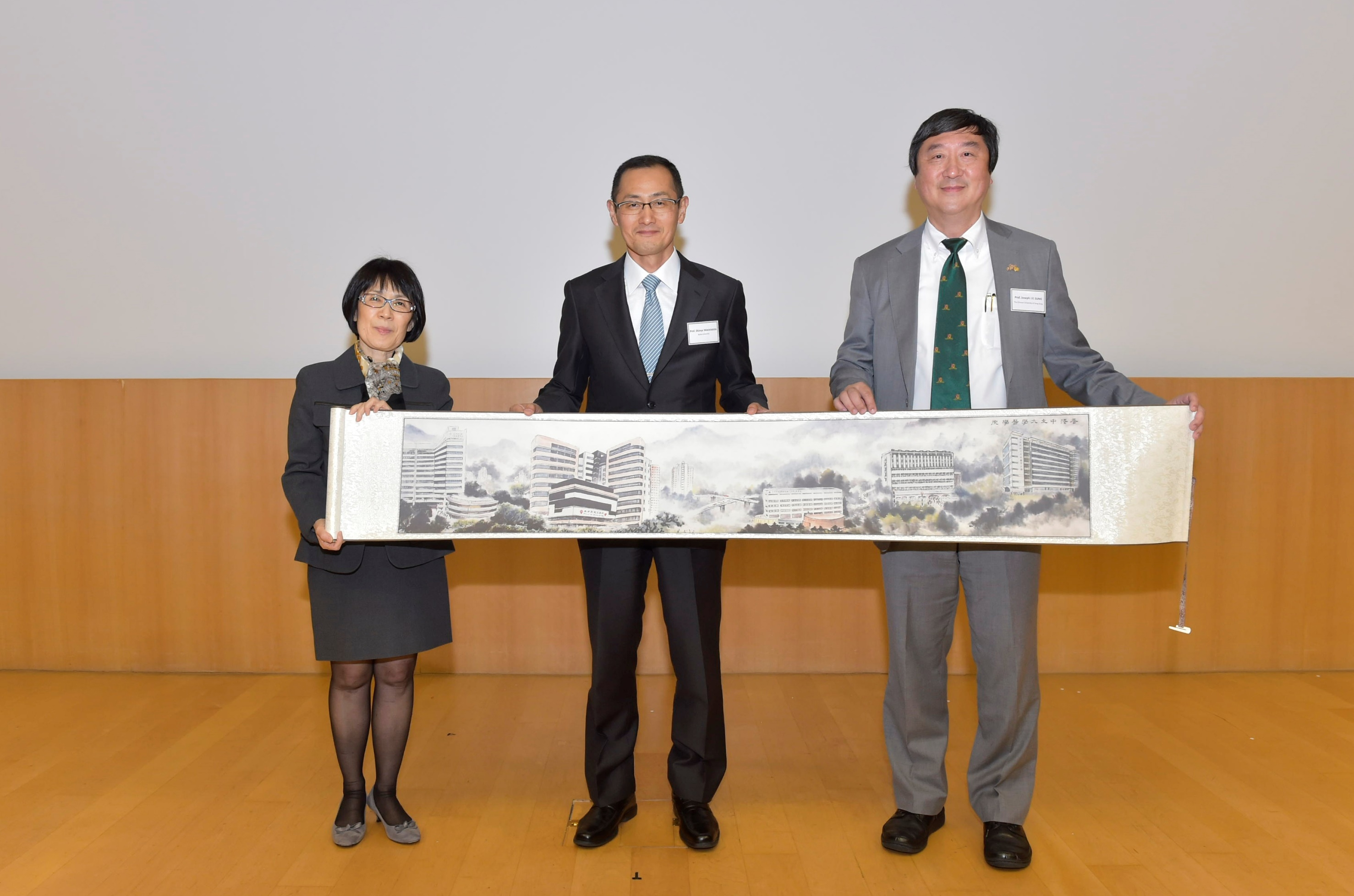 Prof. Joseph J.Y. Sung, Vice-Chancellor and President, CUHK (right) and Prof. Fanny M.C. Cheung, Pro-Vice-Chancellor and Vice-President, CUHK (left) present a souvenir to Prof. Shinya Yamanaka.