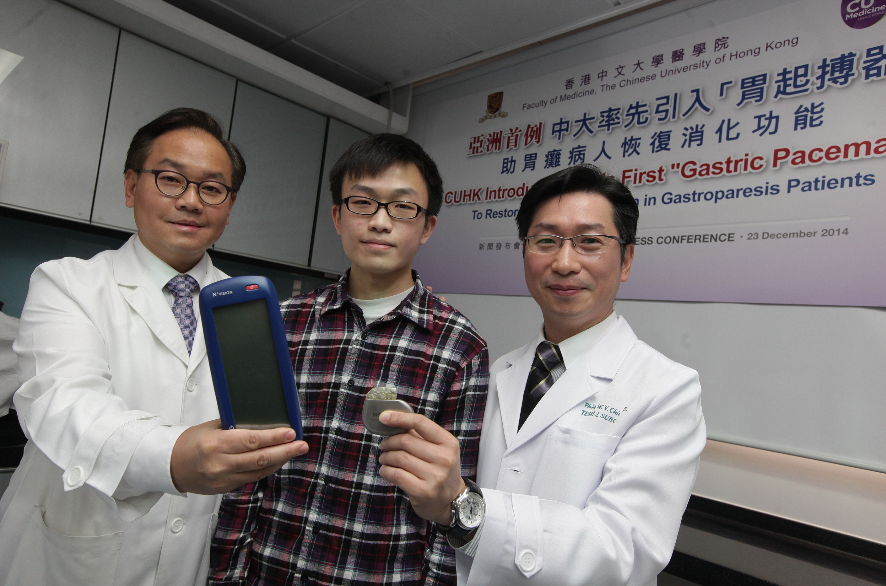 """The patient who underwent Asia's first """"Gastric Pacemaker"""" implant surgery, Chan Chi-kit (middle), and the responsible doctors - Professor CHIU Wai Yan Philip (right), Assistant Dean (External Affairs) of the Faculty of Medicine and Director of the CUHK Jockey Club Minimally Invasive Surgical Skills Centre, and Professor WU Che Yuen Justin (left), Associate Dean (Development) of the Faculty of Medicine and Director of the S.H. Ho Centre for Digestive Health – pose for a group photo. On Professor Chiu's and Professor Wu's hands are the six-centimetre-long """"Gastric Pacemaker"""" and monitor instrument respectively."""