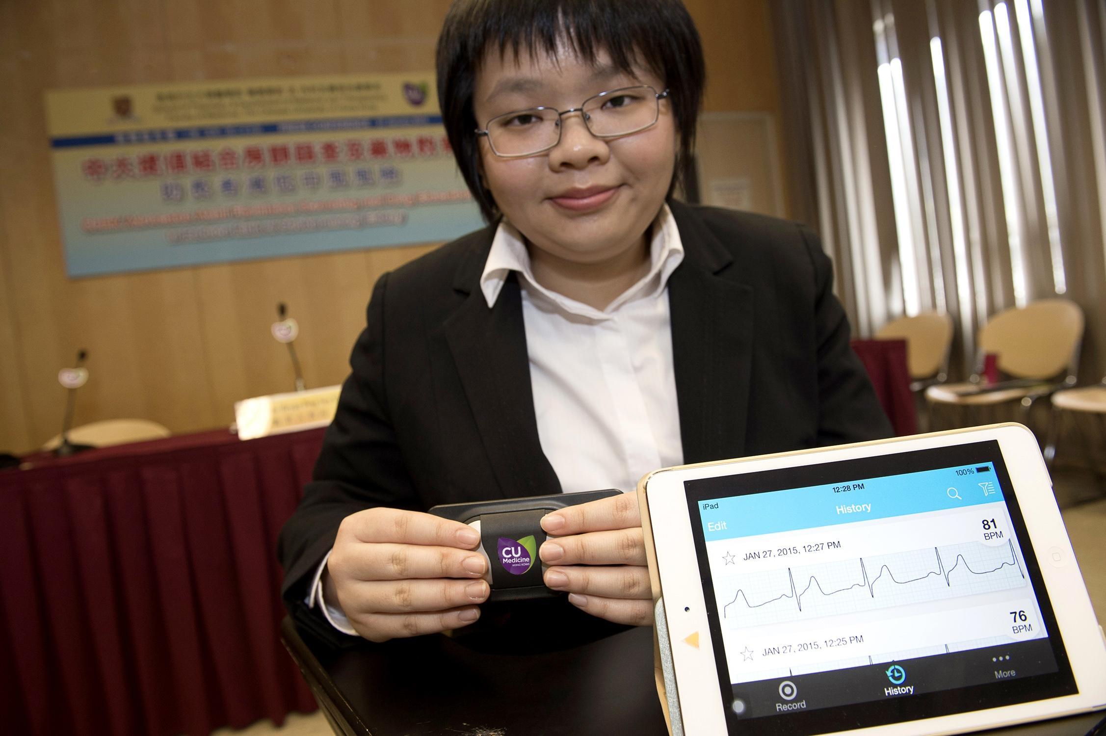 学生义工示范使用手提心电图检测器进行房颤检查。