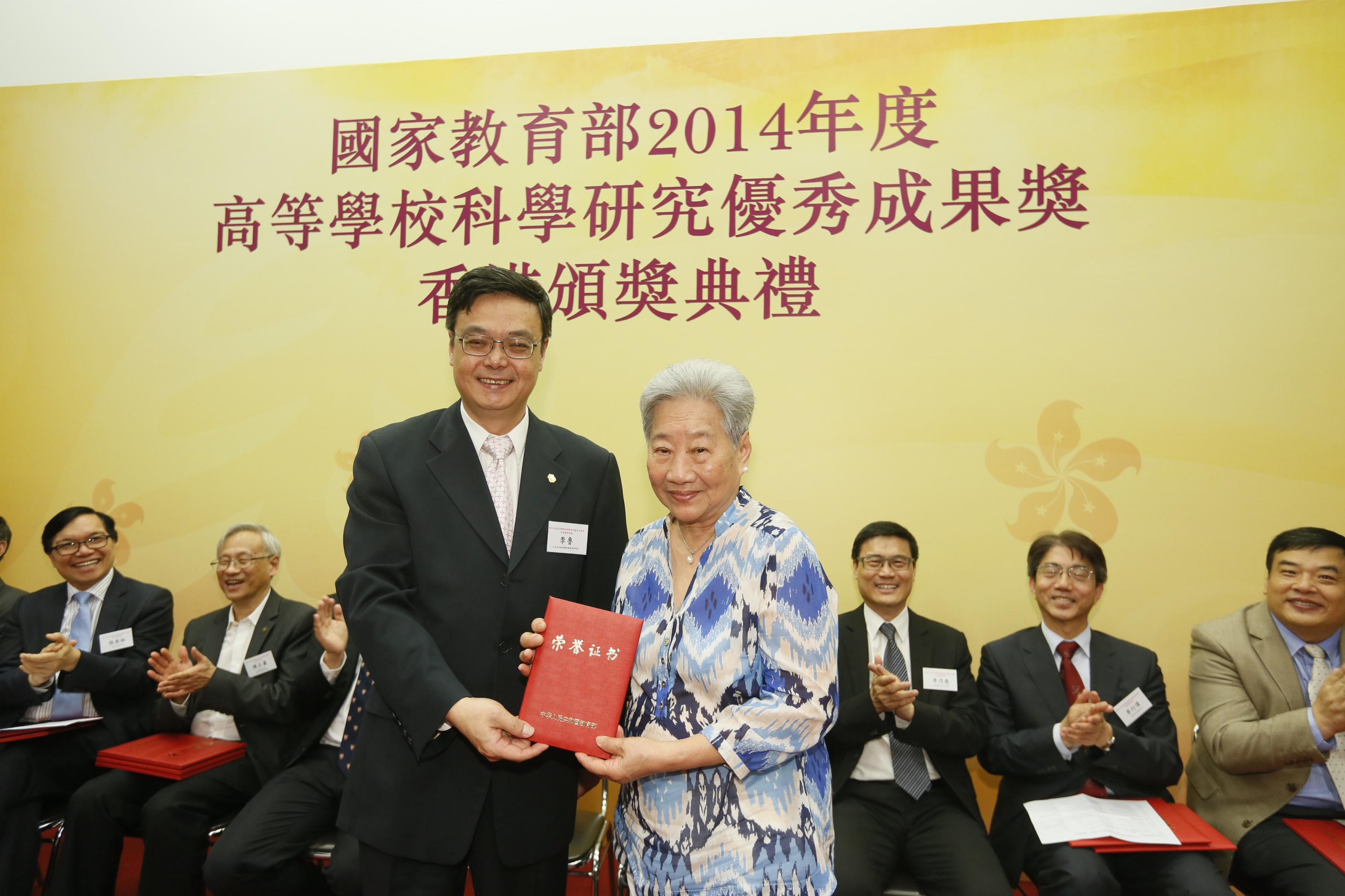 Prof. Tony Mok's mother (right) represents his son to receive the award certificate from Prof. Lu Li.