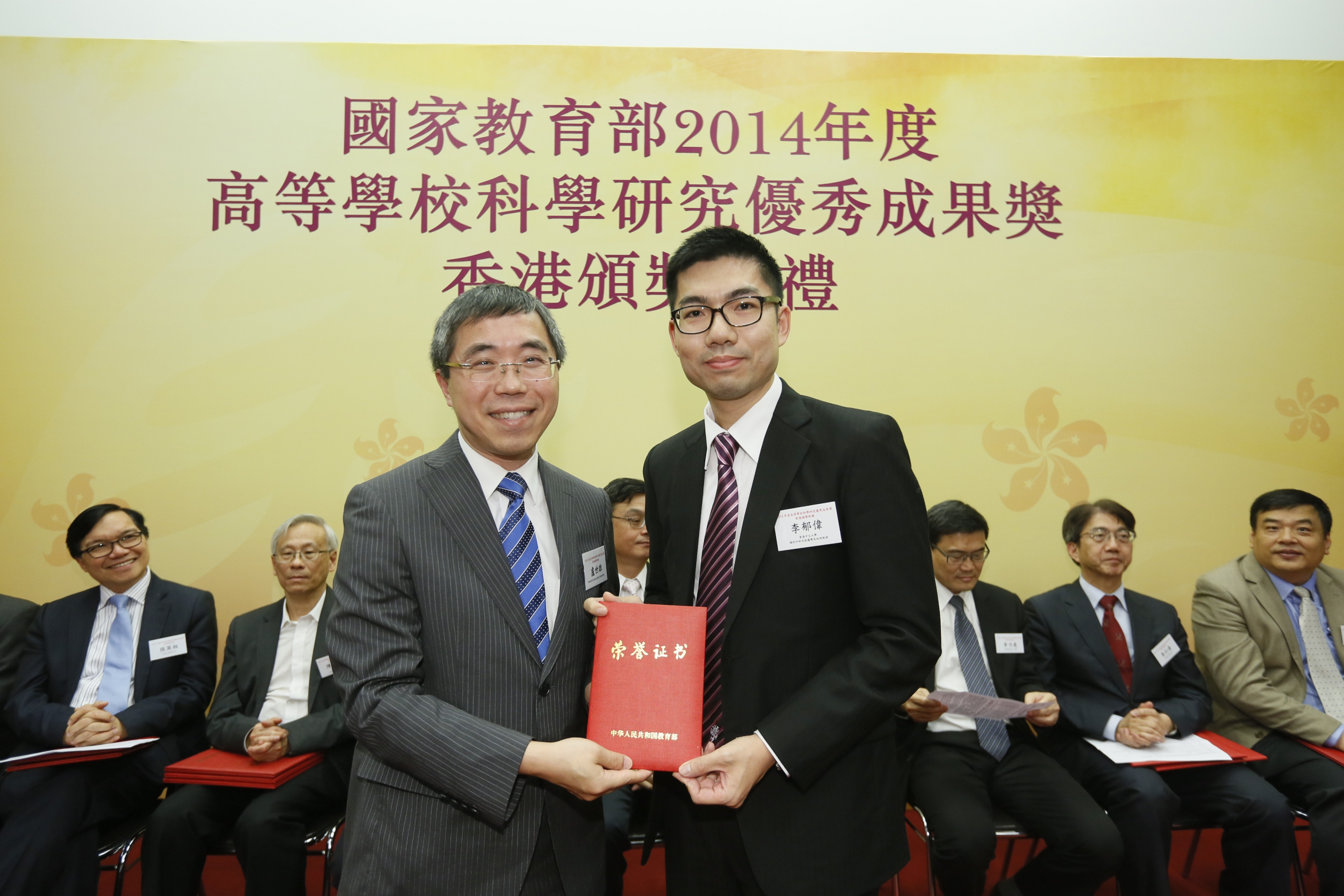 Prof. Yuk-wai Lee (right) represents Prof. Gang Li to receive the award certificate from Mr. Brian Lo, Deputy Secretary for Education, HKSAR Government.