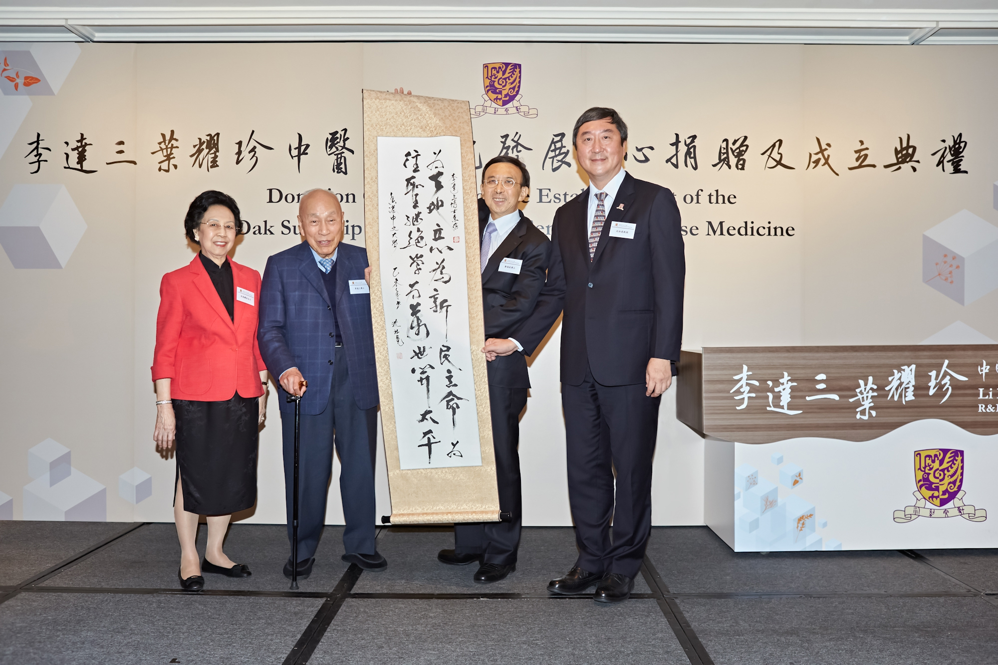 Dr. Vincent Cheng and Prof. Joseph Sung present a calligraphy written by Professor Sung to Dr. and Mrs. Li Dak Sum.
