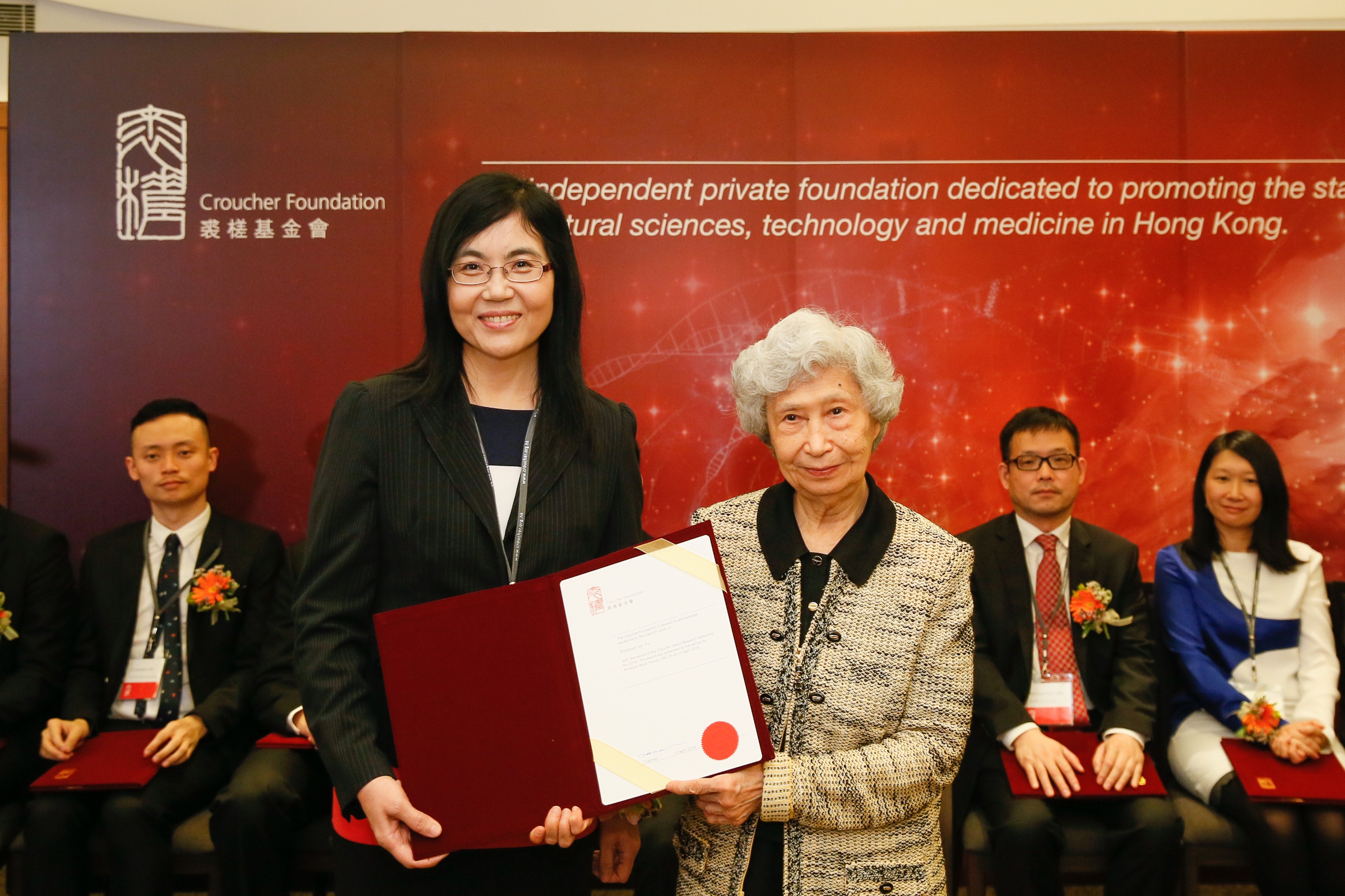 Prof Rosie Young presents the award of Senior Research Fellowship to Prof Jun Yu.
