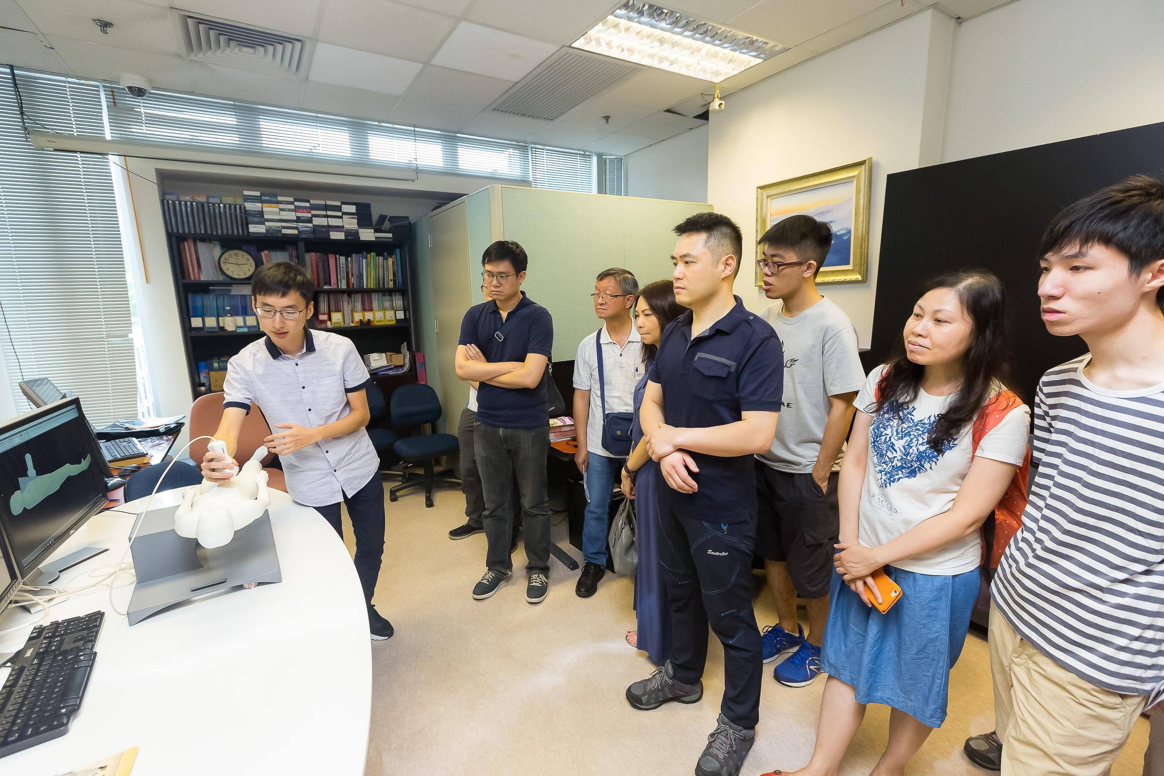 研究人員向校友示範實驗室的科技項目。