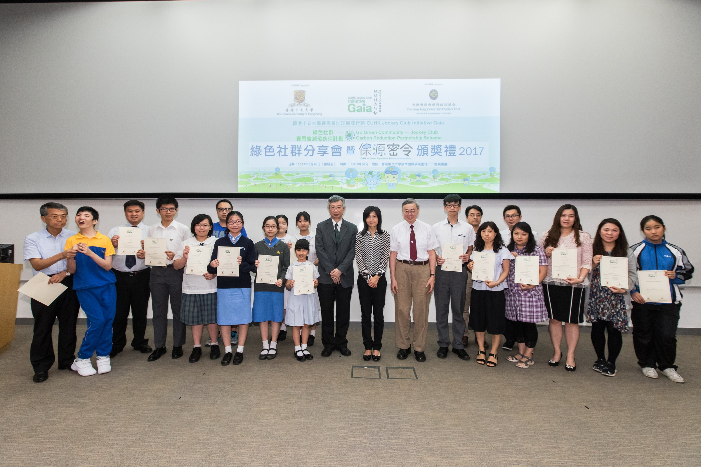 (9th to 11th from right) Prof. Gabriel Lau, AXA Professor of Geography and Resource Management and Director of the Institute of Environment, Energy and Sustainability, CUHK; Ms Vivian Lee, Senior Charities Manager of The Hong Kong Jockey Club; and Prof. Tung Fung, Associate Vice-President of CUHK present certificates of participation to members of the Go Green Community – Jockey Club Carbon Reduction Partnership Scheme.