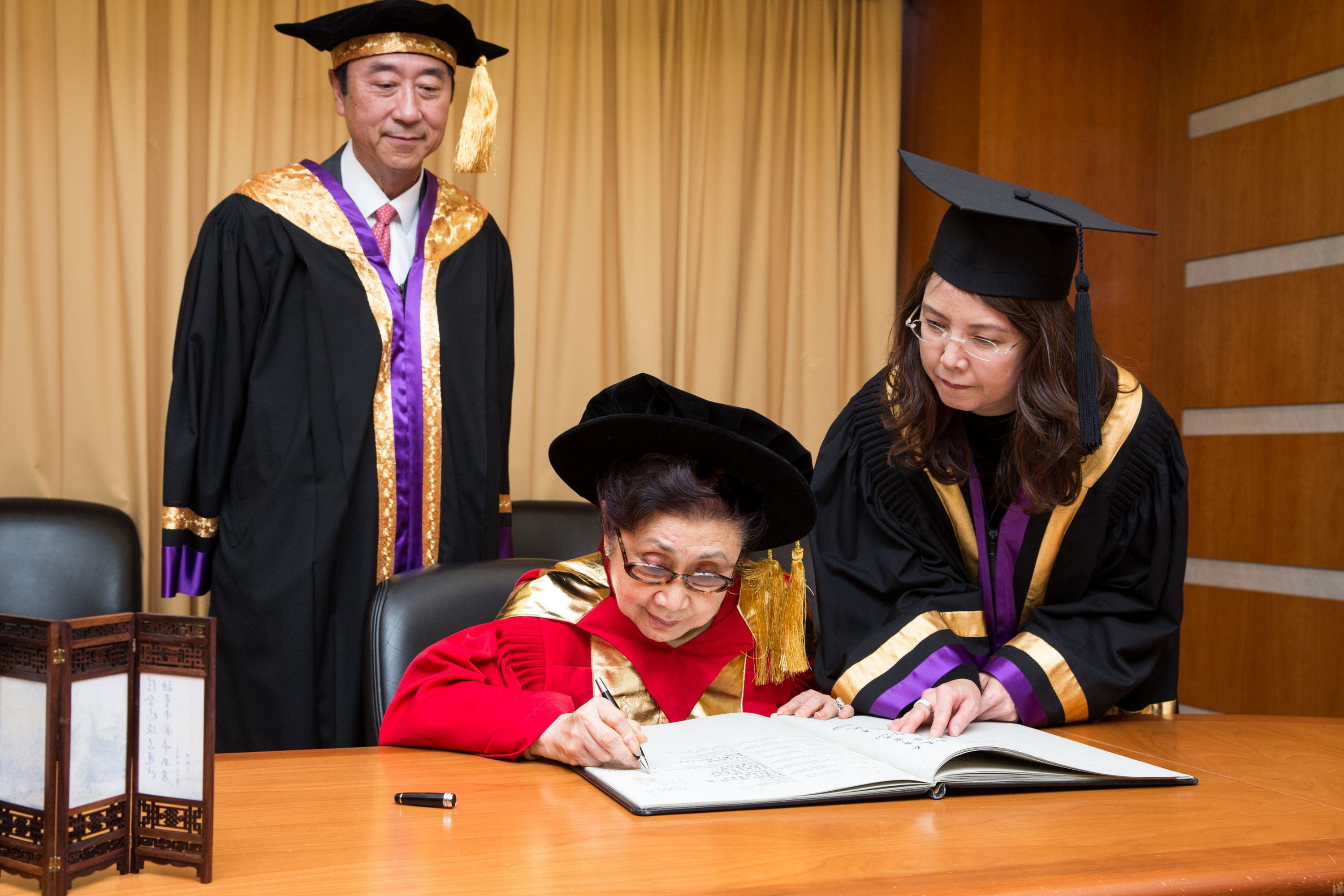 Dr. CHAN Shuk-leung (middle) signs on the Register of Honorary Graduates