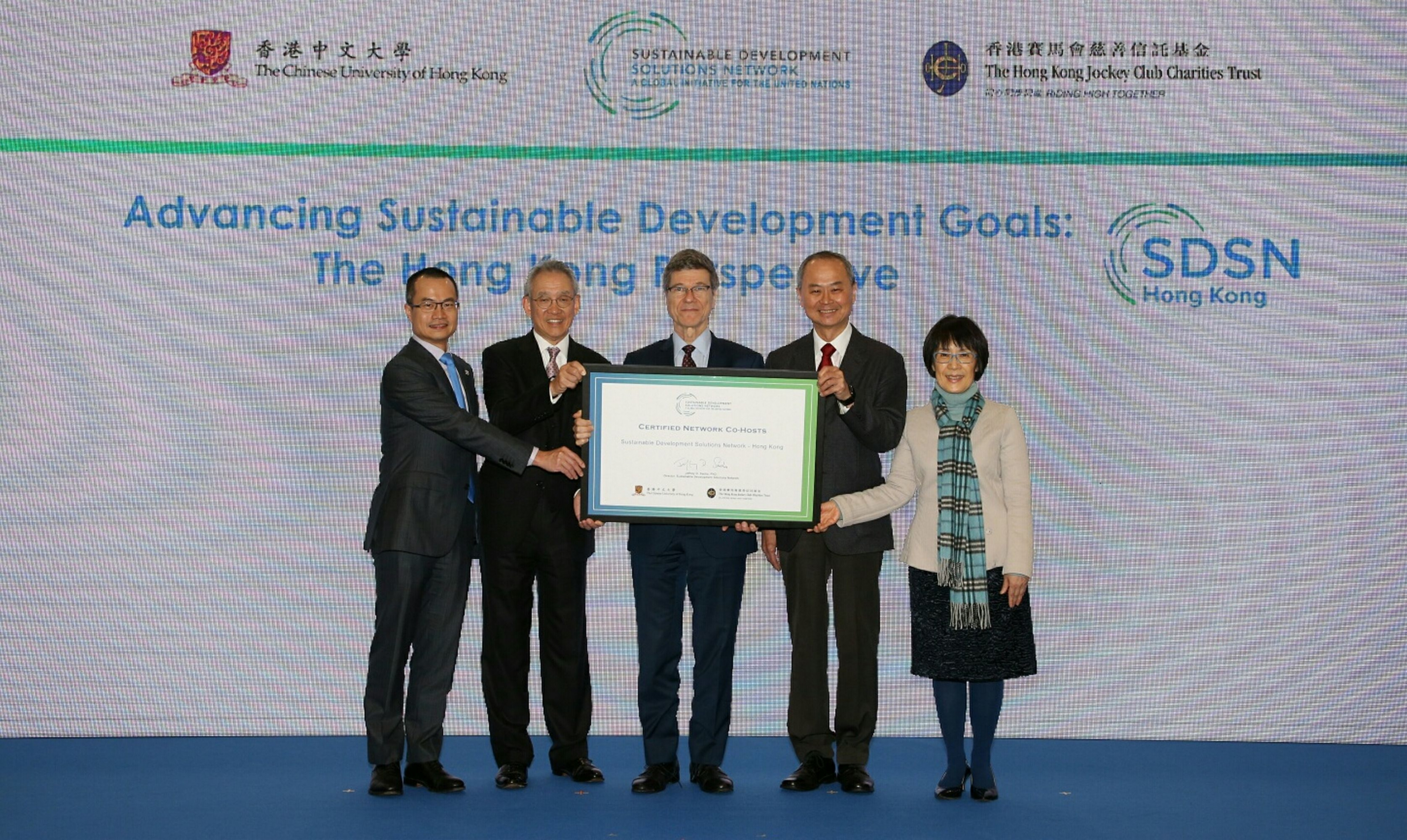 Director of the UN SDSN Professor Jeffrey Sachs (centre) presents SDSN Hong Kong Appointment Certificate to Deputy Chairman of The Hong Kong Jockey Club Mr Anthony W K Chow (2nd left), Pro-Vice-Chancellor of CUHK Professor Fok Tai-fai (2nd right), Executive Director, Charities and Community of The Hong Kong Jockey Club Mr Leong Cheung (1st left) and Pro-Vice-Chancellor of CUHK Professor Fanny Cheung (1st right).
