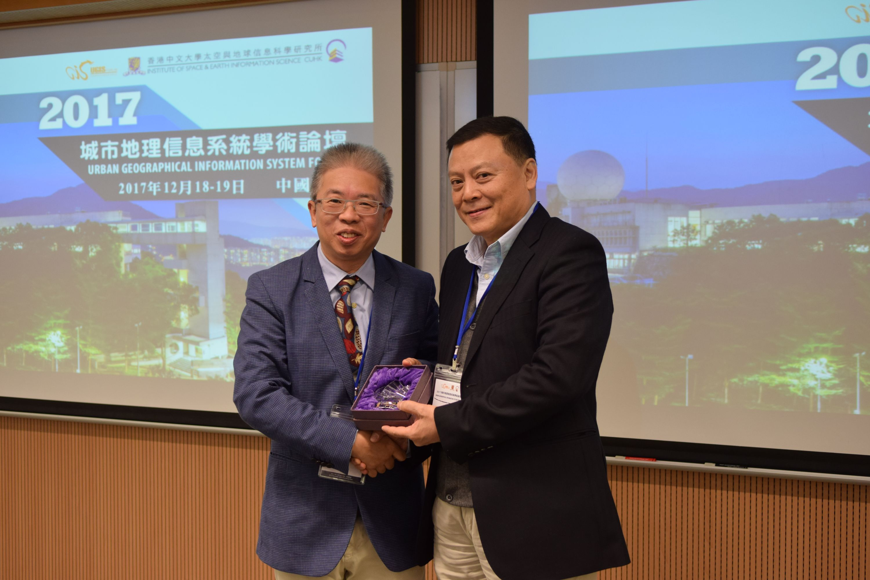 Prof. CHIU Chi Yue, Dean of the Faculty of Social Science, CUHK (left) presents a souvenir to Mr. JIANG Miankang, Secretary General of the UGIS Forum and former President of Shanghai Research Institute of Urban and Rural Construction and Traffic Development.