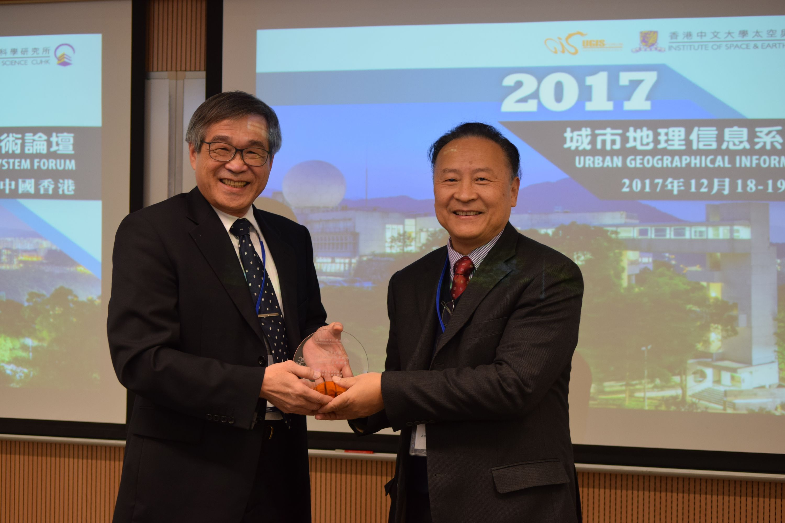 Prof. CHIANG Hun-chin of Taiwan Geographic Information Society (left) presents a souvenir to Prof. LIN Hui, Director of ISEIS, CUHK.