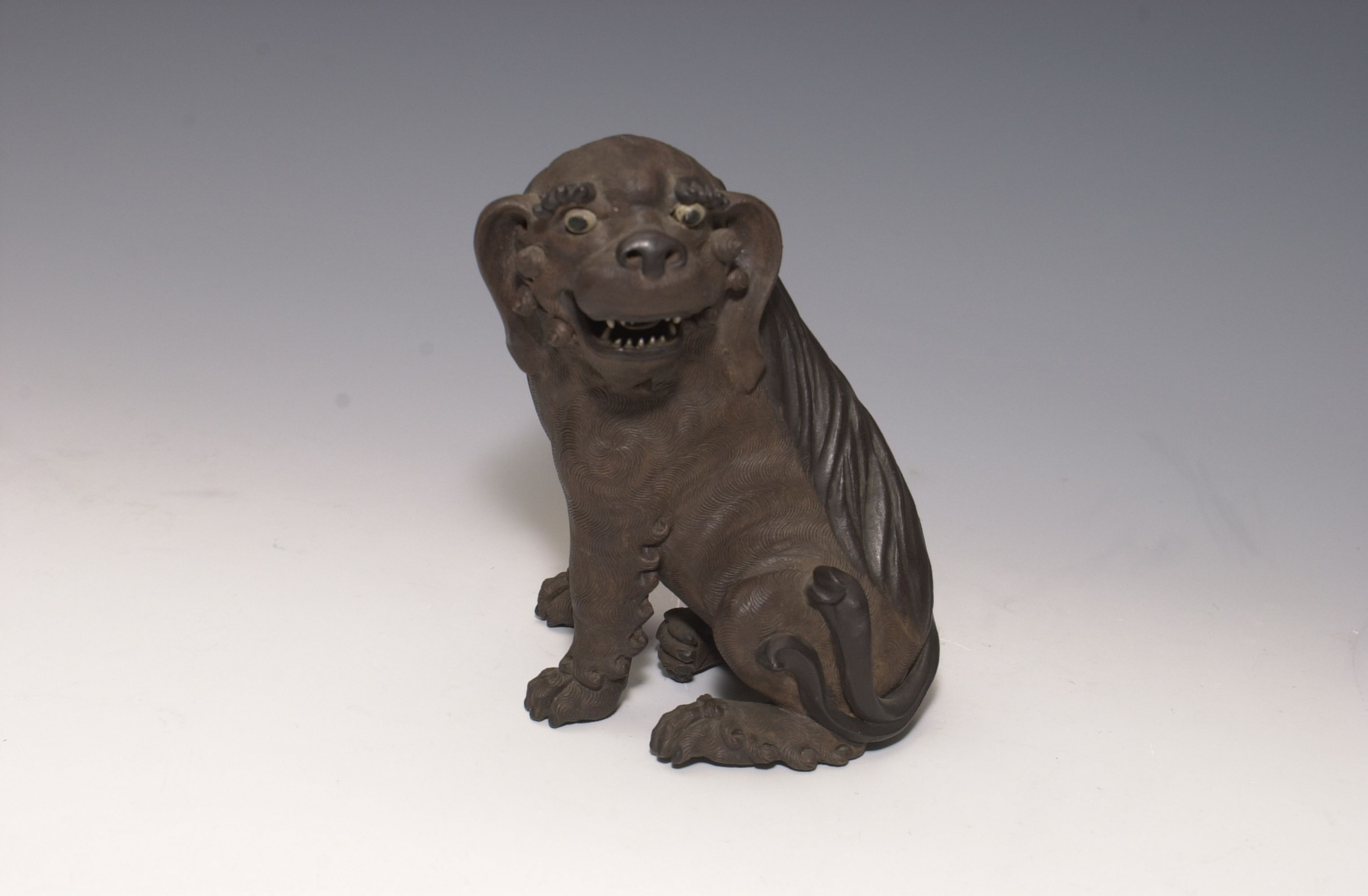 Unglazed Lion Dog Early 20th century, attributed to Huo Jin Shiwan kiln ware of Foshan, Guangdong province Gift of Bei Shan Tang Art museum collection Acc. no. 1981.0065  The Lion dog, also known as Pekingese, is a Chinese ancient breed of small toy dog. This unglazed lion dog came from the Shiwan kiln of Foshan, Guangdong province, whose body was made from the local red clay, with dark brown glaze painted in places like eyes and nose. The sculpture is livened up by its turning head, opening mouth, as well as the impressed fine coat of hair. An elliptical mark on the neck denotes that it is made by the hunchback potter Huo Jin of Shiwan during republic China.