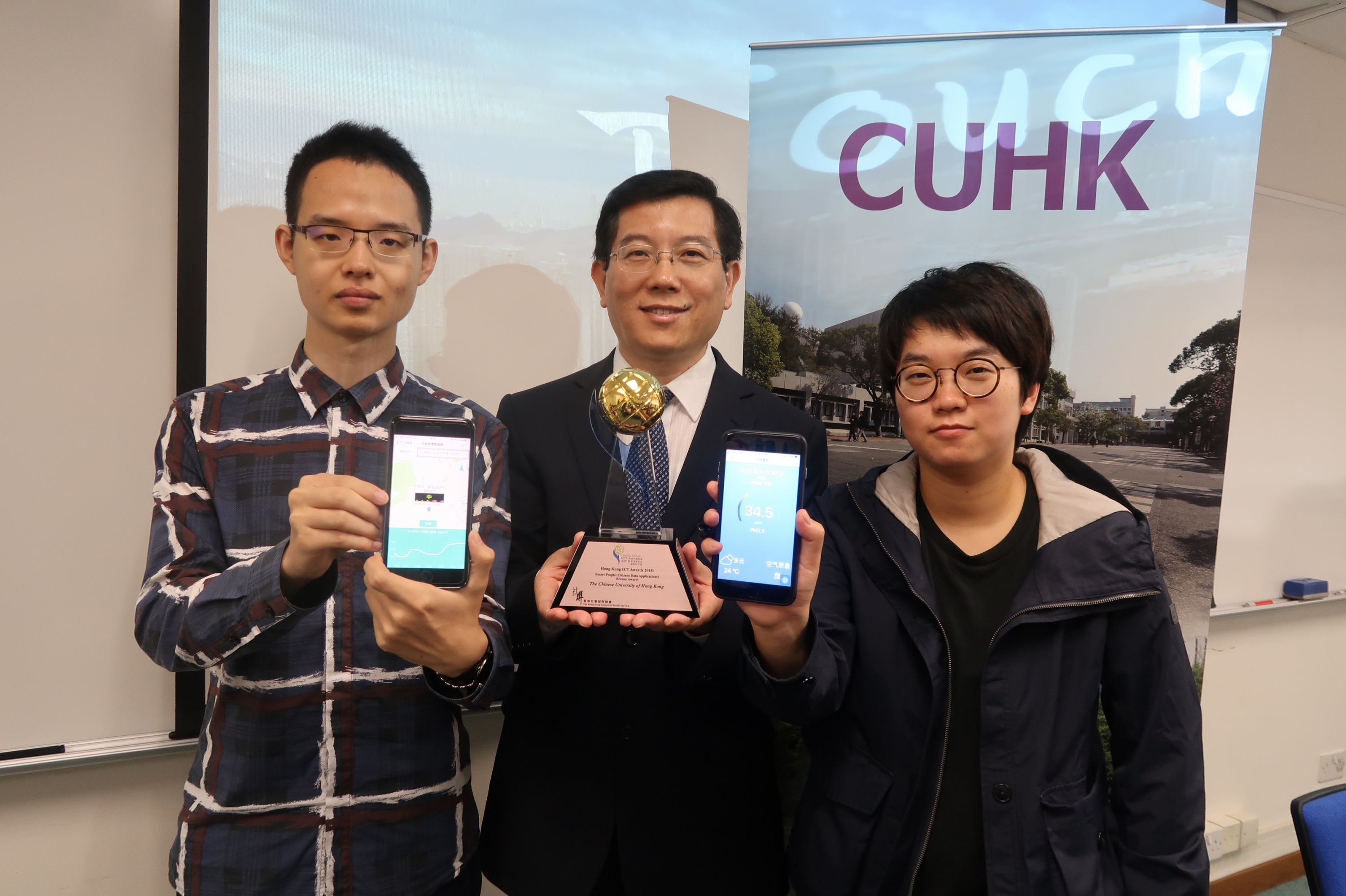"""The """"TouchAir"""" mobile app, developed by Prof. Huang Bo (middle) and his research assistant Tong Xuelian (right) and Sun Peifeng (left), has awarded the ICT award 2018."""