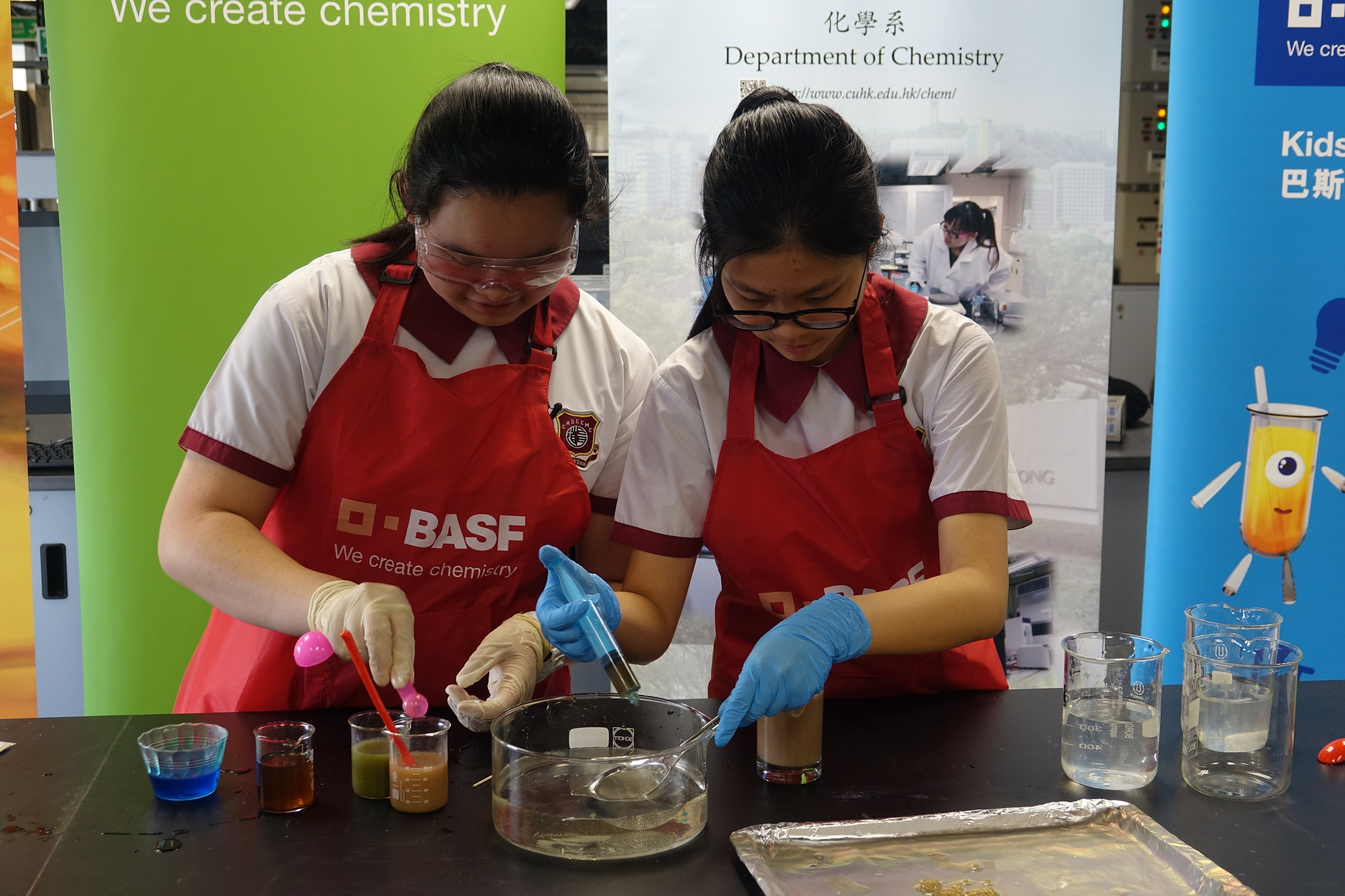 Helia Wong (left) and Phoebe Yeung (right) show the chemical process behind how liquids can be formed into spheres with the use of sodium alginate and calcium lactate.