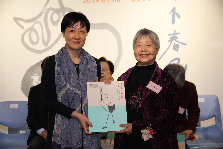 Prof. Xu Xiaodong, Associate Director of the Art Museum, CUHK presents a souvenir to Ting Lai-ka, a daughter of Ting Yin-yung.