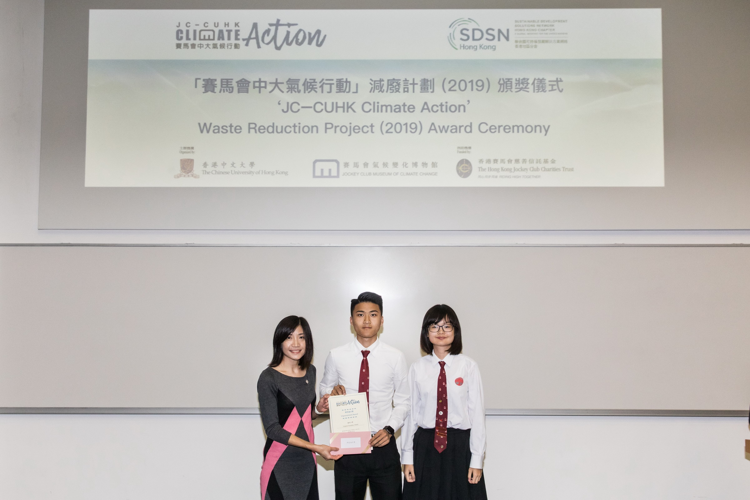 香港賽馬會慈善事務經理李穎詩女士頒發嘉許證書予參與「減廢計劃」的學校及學生。