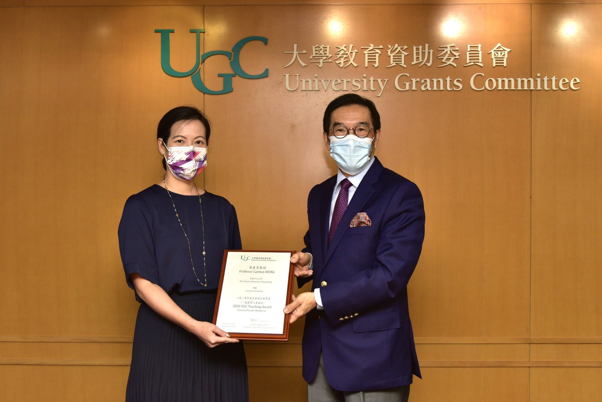 Dr. Carmen Wong (left) receives the award certificate from Mr. Carlson Tong, Chairman of UGC. (Photo provided by the organiser)