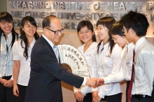 """Dr Li Ka-shing receives a paper fan with an inscription """"Knowledge reshapes destiny, scientific research constructs people's livelihood"""" from a group of medical students of CUHK."""