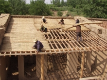 Villagers use simple tools and natural materials to build the school