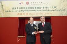 Professor Lawrence J. Lau presents a souvenir to Mr Zhan Yongxin (left)