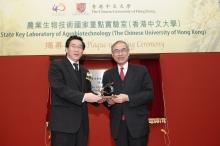 Professor Lawrence J. Lau presents a souvenir to Mr Li Ling (left)