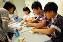 小學生在義工帶領下學習摺紙。