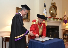 Professor Levin (right) signs on the Register of Honorary Graduates.
