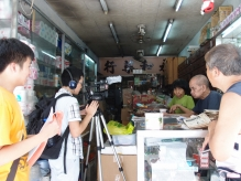 Mr. and Mrs. Ho, the owners of Wing Wo Pharmacy in Sai Ying Pun, are interviewed by two participating students.