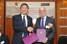 Prof. Joseph J. Y. Sung (left) and Prof. Andrew Hamilton shake hands after the agreement has been renewed.