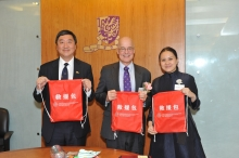 Prof. Emily Y. Y. Chan (left) presents CCOUC rescue bags as souvenir to Prof. Joseph J. Y. Sung, (right) and Prof. Andrew Hamilton.