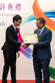 Professor Tuan presents certificates to a student.