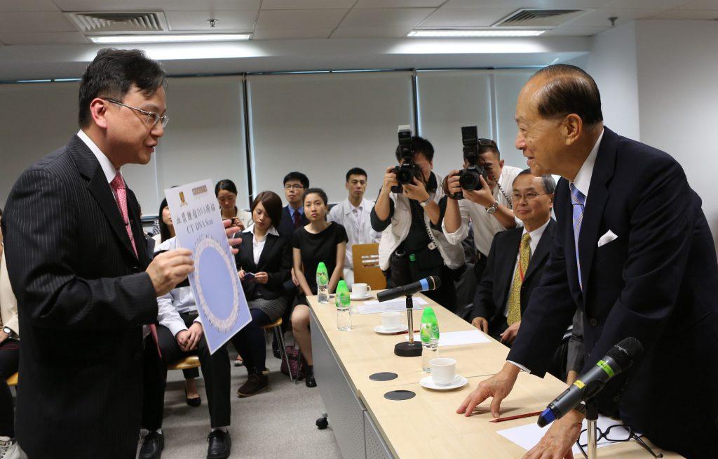 (左一) 中大李嘉誠健康科學研究所所長盧煜明教授向基金會主席李嘉誠先生 (右一)介紹利用血漿作癌症檢測的先進技術。右二為中大學副校長霍泰輝教授。