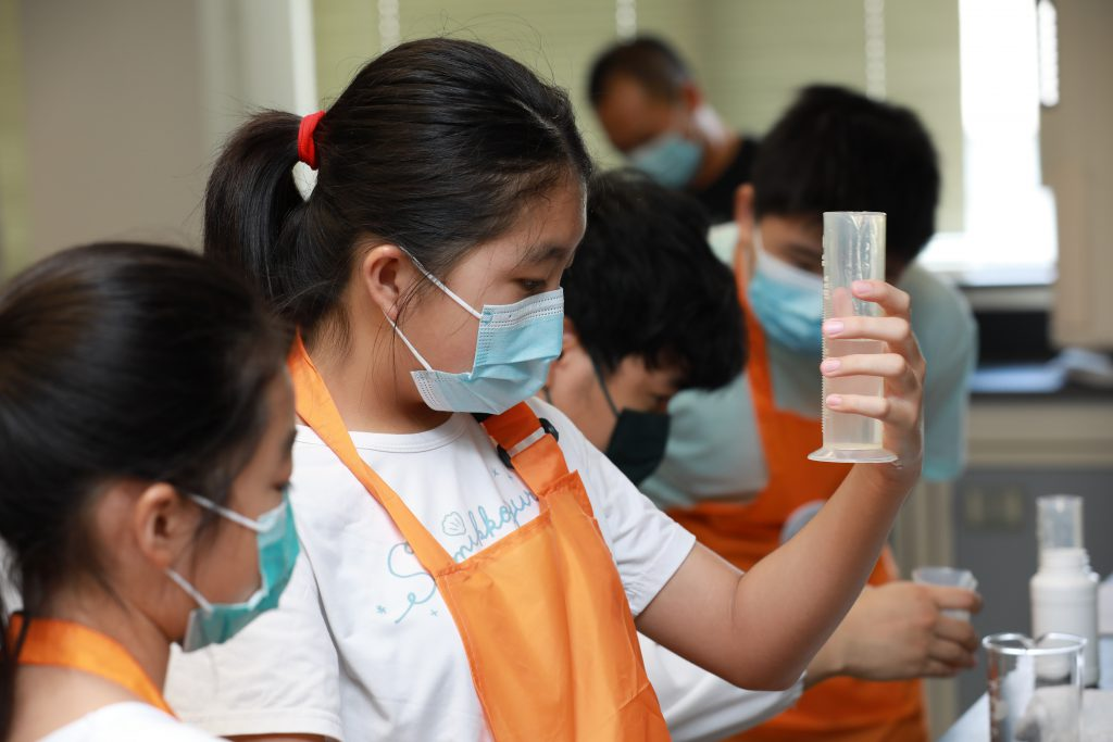 A student carefully measuring the ingredients of the hand sanitiser