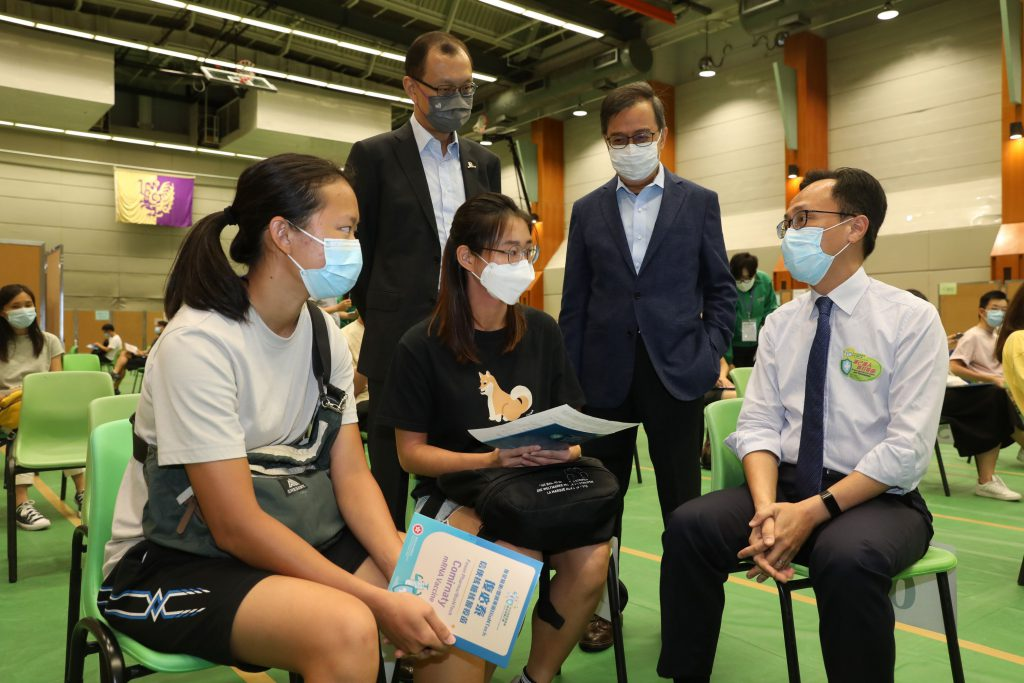 Mr. Patrick Nip, Professor Alan Chan and Mr. Eric Ng communicate with CUHK members participating in the outreach vaccination service.